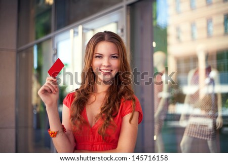 Young beautiful girl holding a blank credit card outdoor against store background - stock photo
