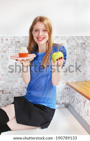 Young beautiful girl holding cupcake and apple in her hands