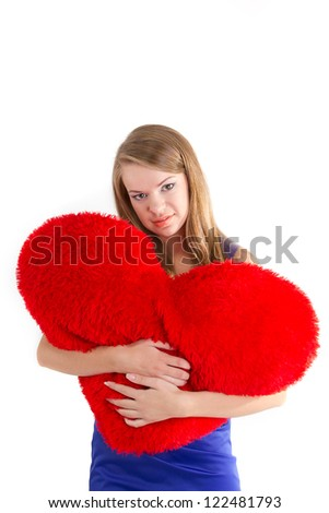 Young beautiful  girl  hugs a big soft heart. Feast of St. Valentine's Day.