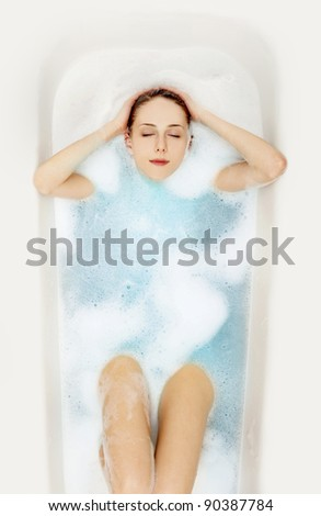 Young beautiful girl in a bath with foam - stock photo