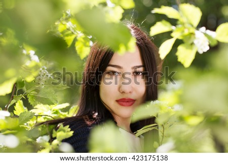Young beautiful girl in a blossoming spring garden. - stock photo
