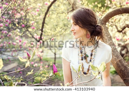 Young beautiful girl in a blossoming spring garden. Boho style. Portrait in profile, close-up. Girl in the necklace and earrings.Girl in the sunset light. Woman enjoying the blooming magnolia. - stock photo