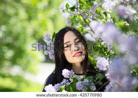 Young beautiful girl in a blossoming spring garden. The blossoming lilac - stock photo
