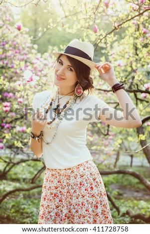 Young beautiful girl in a blossoming spring magnolia garden. The girl in the garden morning. Boho style. Portrait, close-up. The girl in the hat, necklace and earrings. Toned. - stock photo