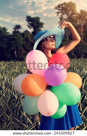 Young beautiful girl in a blue hat with colorful balloons in vintage glasses