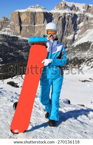 young beautiful girl in a blue ski suit standing leaning on snowboard mountains in the background - stock photo