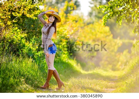 young beautiful girl in a cowboy hat, country style - stock photo