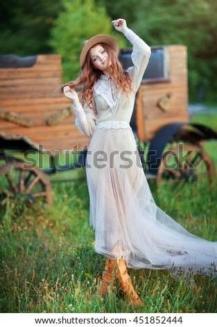 Young beautiful girl in a cowboy hat, vintage dress and leather boots posing and looking at camera. Colorful photo of  pretty long hair model outdoor.Country style.Art work. - stock photo