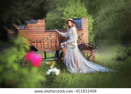 Young beautiful girl in a cowboy hat, vintage dress and leather boots posing near western coach and looking at camera. Colorful photo of  pretty long hair model outdoor.Country style.Art work. - stock photo