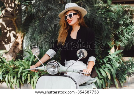 young beautiful girl in a hat in a black t-shirt white pants and sneakers posing on a vintage scooter  in Italy fashion clothing and accessories bracelet on her arm red lipstick on her lips sunglasses - stock photo