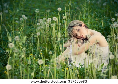 Young beautiful girl in a light summer dress sits in a clearing overgrown with white fluffy dandelions in the summer park