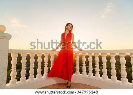 young beautiful girl in a red dress standing next to the stone gazebo with the sunset in the background - stock photo