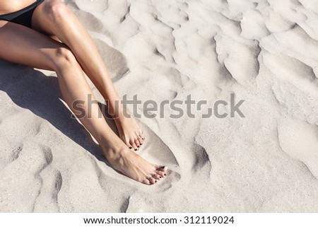 Young beautiful girl in a striped black bikini sunbathing on the soft sandy sea shore. Outdoor lifestyle picture on a hot sunny summer day. - stock photo