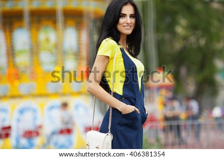 Young beautiful girl in a summer dress standing on the background of the carousel. Summer shot. - stock photo