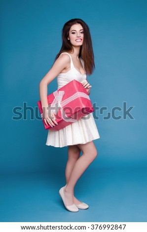 Young beautiful girl in a white dress with a gift in red wrapping paper on a blue background