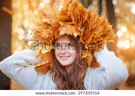 Young beautiful girl in autumn park with a wreath of yellow leaves on the head - stock photo
