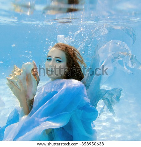 young beautiful girl in blue dress as aqua element with shell in her arms underwater  - stock photo