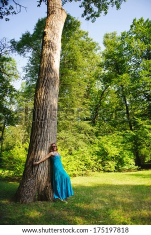 Young beautiful girl in blue dress near huge tree - stock photo