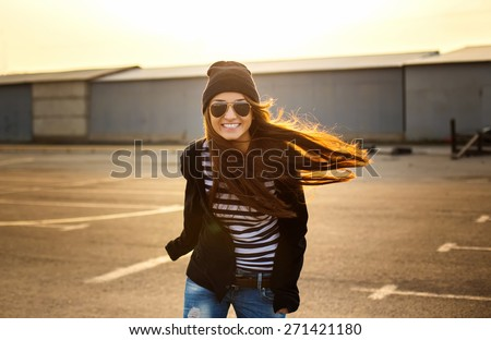 Young beautiful girl in glasses runs at sunset along the streets of the city. - stock photo