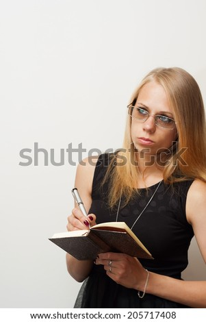 young beautiful girl in glasses thoughtfully writes something in a notebook ballpoint metal pen