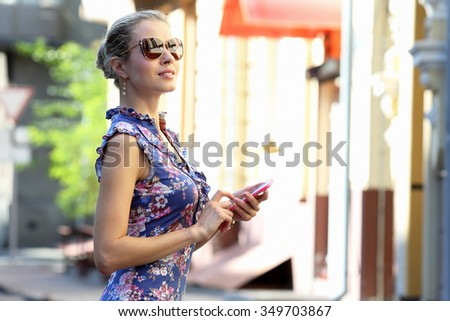 young beautiful girl in glasses with phone in hand looking to the side