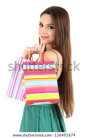 Young beautiful girl in green dress holding bright  shopping bags, isolated on white