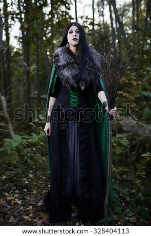Young beautiful girl in green raincoat, looks as witch on Halloween in forest