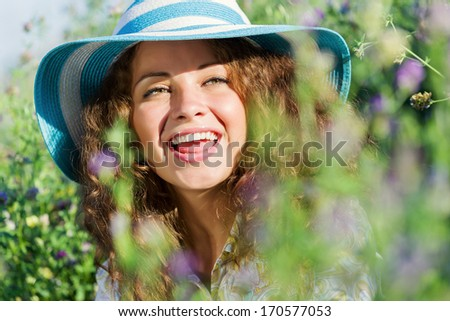 Young beautiful girl in hat and glasses sitting in grass