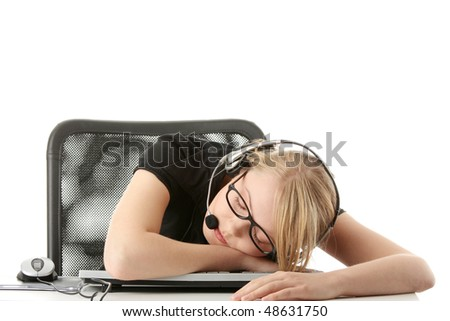 Young beautiful girl in headset,sitting at the desk and sleeping, isolated on white background  (call center or e learning concept) . - stock photo