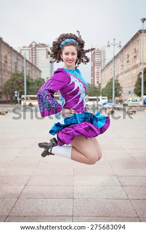 Young beautiful girl in irish dance dress and wig jumping outdoor - stock photo