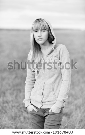 Young beautiful girl in jacket with hood against autumn nature. - stock photo