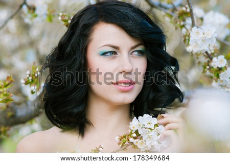 young beautiful girl in spring blooming garden