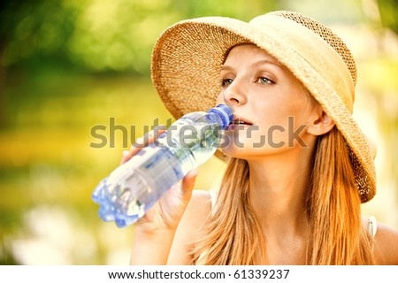 Young beautiful girl in straw hat against lake in city park drinks water from plastic bottle. - stock photo