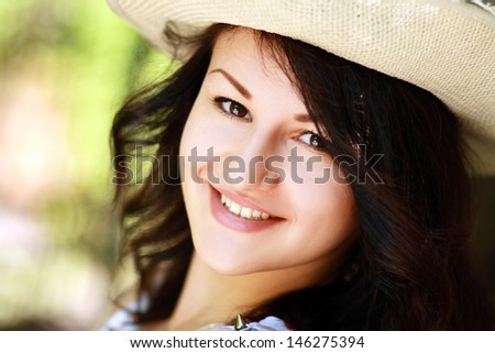 Young beautiful girl in straw hat against park