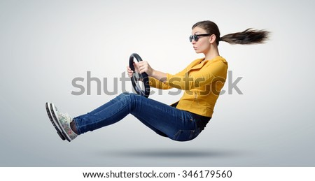 Young beautiful girl in sunglasses driver car with a wheel, auto concept