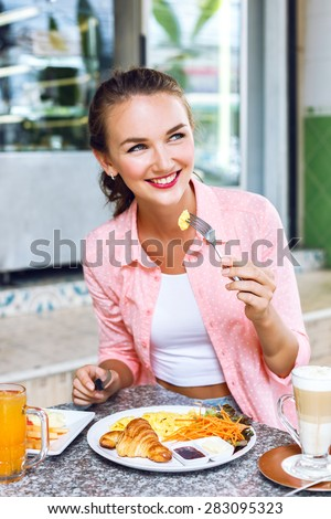 Young, beautiful girl in the breakfast cafe. She ordered scrambled eggs, croissant, latte and orange juice. Looking nice and cute and fresh.