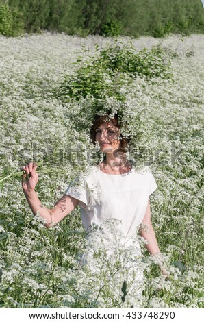 Young beautiful girl in the floral field with a wreath on a head, summer nature.