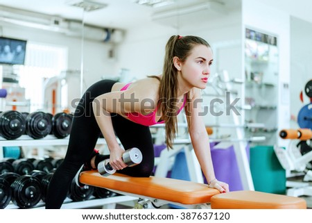 young beautiful girl in the gymathletic woman pumping up muscles with dumbbells