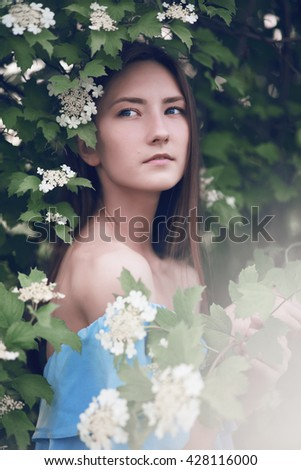 young beautiful girl in the park with flowers