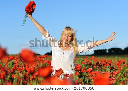Young beautiful girl in the poppy and wheat field