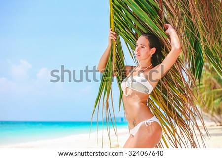 Young beautiful girl in white bikini on tropical beach with palm leaf