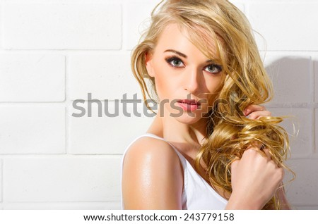 Young beautiful girl in white swimsuit on white wall (normal version) - stock photo