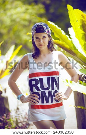 Young beautiful girl in white t-shirt in the tropical woods. Portrait of hupster woman in tropical forest. fashionable teenage model in summer meadow, outdoor shot. Cute brunette female in flower cap. - stock photo