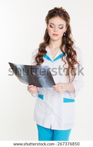 Young beautiful girl intern looking at the x-ray picture of knee isolated on white - stock photo