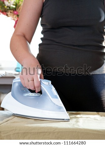 young beautiful girl ironing clothes - stock photo