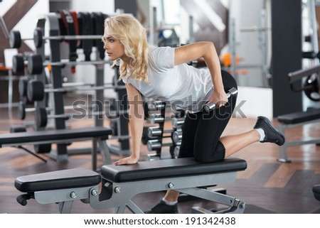 young beautiful girl is doing exercises at the gym and smiling
