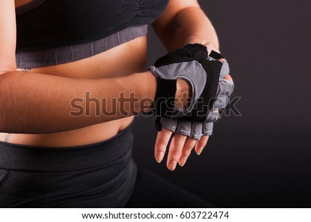 Young beautiful girl is engaged in fitness on a black background. Sports girl in black clothes is engaged in fitness