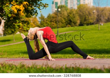 Young beautiful girl is engaged in yoga, outdoors in a park in summer
