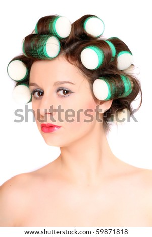 Young beautiful girl is having hair curlers on her head. High key studio portrait. - stock photo