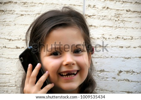 Young beautiful girl is using a mobile phone outdoors.